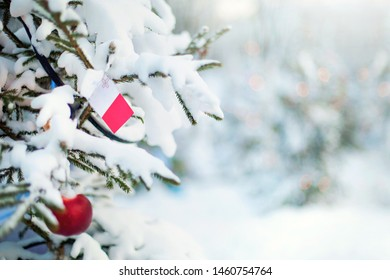 Christmas Malta. Xmas tree covered with snow, decorations and a flag of Malta. Snowy forest background in winter. Christmas greeting card.