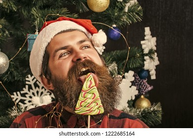 Christmas man with beard on happy face and lollipop. santa claus man in hat at decoration. Party celebration and blowjob. Winter holiday and xmas. New year guy lick candy or sweet.
