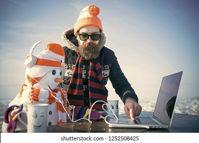 Christmas man with beard on happy face. xmas leisure and new technology. Snowman, winter holiday celebration. Santa claus man with snowman in hat. New year guy with laptop and headset, audio book.