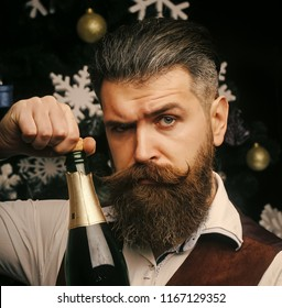 Christmas man with beard on serious face open champagne. New year guy with wine bottle. santa claus man celebrating, alcohol. Winter holiday and xmas. Party celebration and drink.