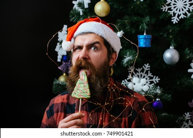Christmas man with beard on surprised face and lollipop. New year guy lick candy or sweet. santa claus man in hat at decoration. Winter holiday and xmas. Party celebration and blowjob.