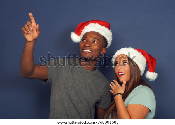christmas man and women wearing santa claus red hat pointing up and smiling surprise
