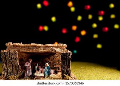 Christmas Manger scene bethlehem portal with figures including Jesus, Mary, Joseph, cow and mule with unfocused lights on black background. Nativity scene