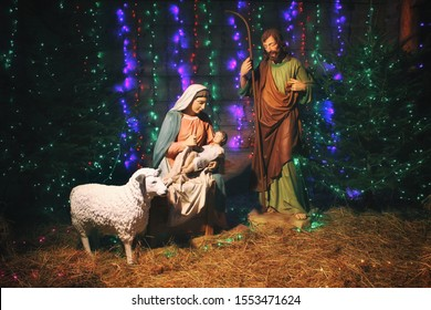 Christmas Manger scene with figures including Jesus, Mary, Joseph, sheep and magi. Christmas background