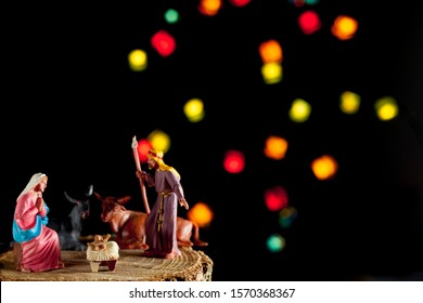 Christmas Manger scene with figures including Jesus, Mary, Joseph, cow and mule with unfocused lights on black background