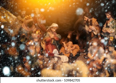 Christmas Manger scene with figurines including Jesus, Mary, Joseph, lamb. Baby birth at holy night in snow and snowflakes