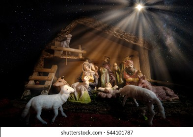 Christmas Manger scene with figurines including Jesus, Mary, Joseph, sheep, magi and the Christmas star with galaxy on the sky.