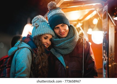 Christmas market at evening, young couple in fairy surroundings