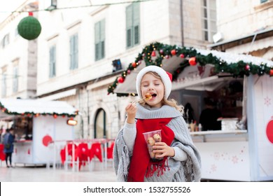 Christmas market. Kid is eating italian fast food. Cute child is tasting festive sweets, fritters, chocolate doughnuts outside in old town street. Cozy fair atmosphere in Dubrovnik, Croatia