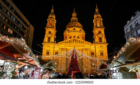 Christmas market on Vorosmarty square before Saint Stephen basilica (translation: I am the way the truth and the life)  in the evening lights - Budapest, Hungary
