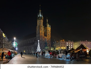 Christmas market and row of horse carriages on the Main Square of Krakow in front of the St. Mary's Basilica in night, Poland