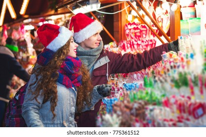 Christmas market shopping, young couple choosing things for buying