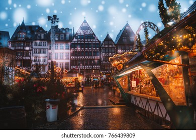 Christmas market spirit during snow night. Celebrating Xmas holidays. Lights, carousel, small houses at the market in the city center with amazing food selection. Frankfurt, Germany. December 1, 2017