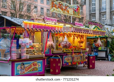"Christmas market in Wuppertal-Barmen, Germany. December 2017. On the banner at the top it says ""Merry Christmas"", The inscriptions on the kiosk means: ""chocolate fruits, apple, fresh popcorn, roasted"