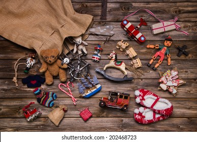 Christmas memories in childhood: old and tin toys on wooden background for gifts.