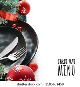 Christmas menu concept with black plates and cutlery decorated with Christmas tree twigs and baubles, isolated on white, text space