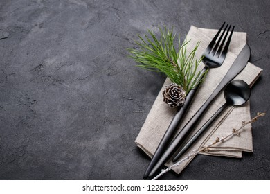 Christmas menu concept . Flat lay with Xmas decorations and pine cones, dark  fork and knife set with napkin. Copy space