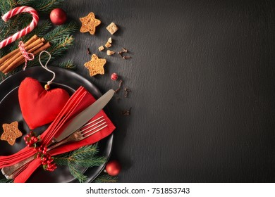 Christmas menu concept on dark stone slate background. Black plates and vintage cutlery with Christmas decorations in green, red and orange. Space for your text on stone.