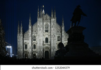 Christmas in Milan, Italy. The Duomo cathedral facade and a giant Christmas tree are illuminated at night.