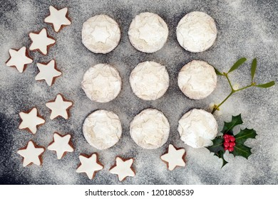 Christmas mince pies and gingerbread cookies with holly berry leaf sprig, mistletoe and icing sugar dusting, fresh baked food for the holiday season. Flat lay.