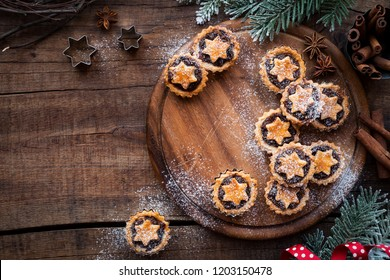 Christmas mince pies  on wooden cutting board with anise and cinnamon stick and festive xmas decorations. Overhead view