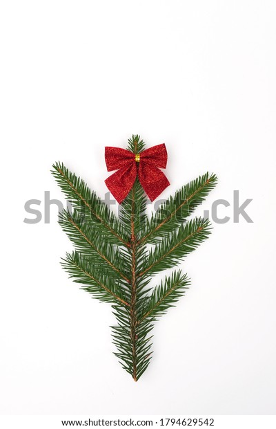 Christmas minimal composition. A branch of a Christmas tree decorated with a red bow isolated on a white background. Copy space.