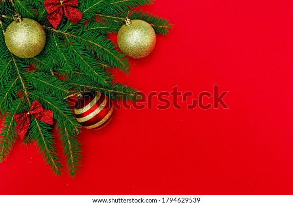 Christmas minimal composition. The branches of the Christmas tree are decorated with gold balls and a bow, isolated on a red background. New Year concept. Copy space.