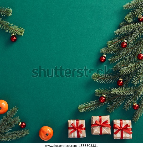 Christmas minimal concept - creative Christmas tree with red bauble and tangerine on dark green background. Copy space. Winter festive decoration. Christmas card concept.