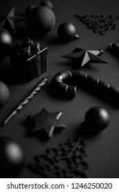 Christmas minimalistic and simple composition in mat black color. Christmas gifts, decorations on black background. Flat lay, top view .