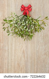 Christmas mistletoe bunch with red bow on light oak background.