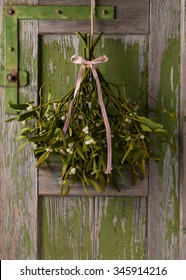 Christmas mistletoe with white and red ribbon bow hanging on a rustic green wooden door.