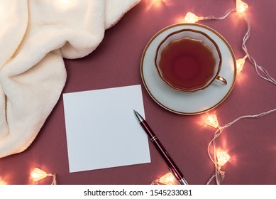 Christmas Mock up with blank white paper sheet, cup of tea, light garland. Top view reativity mockup for to do plans, ideas, art works compositions. Winter new year and christmas xmas Flat lay