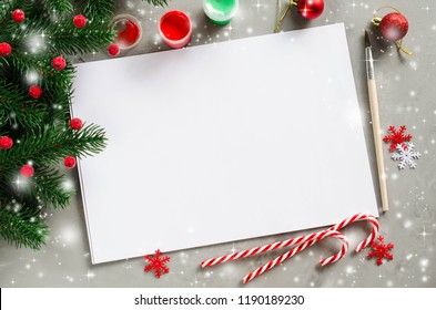 Christmas mock up for greeting card or letter to Santa. Xmas background with empty white paper, paints and fir branches. Copy space, snow effect. View from above.