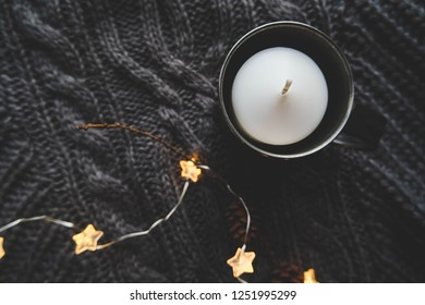 Christmas mock up top view with christmas star garland and candle over knitted plaid.  Warm festive winter backdrop. Cozy hugge atmosphere with candle in metal mug top view, for greeting card.