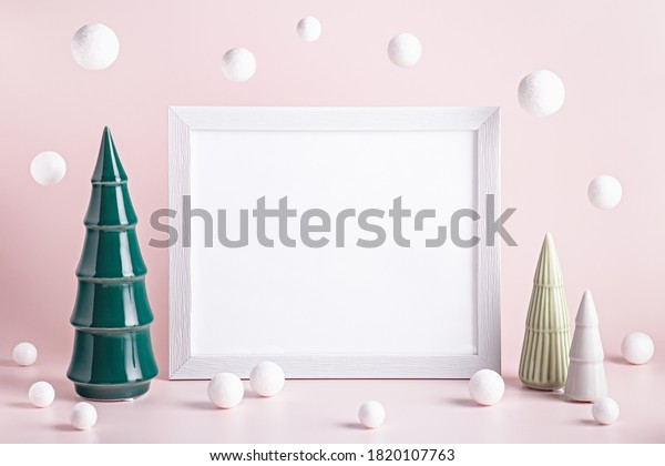Christmas mockup frame with ceramic Christmas trees and white baubles on pink background. Minimalistic Christmas card with modern decor, copy space