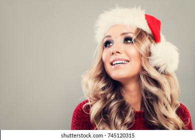 Christmas Model Woman Looking Up. Cute Girl wearing Santa Hat on Background with Copy space