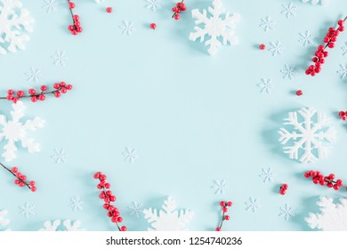 Christmas modern composition. Frame made of red berries and snowflakes on pastel blue background. Christmas, New Year, winter concept. Flat lay, top view, copy space