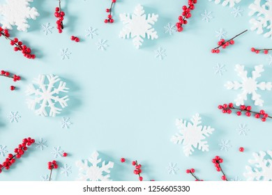 Christmas modern composition. Frame made of green fir tree branches, red berries and snowflakes on pastel blue background. Christmas, New Year, winter concept. Flat lay, top view, copy space