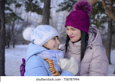 Christmas moments, winter picnic in a forest glade, happy mother and daughter walking in the Park in winter
