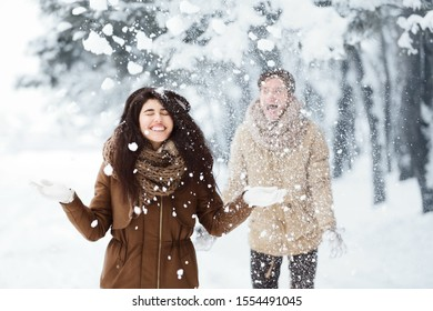 Christmas Mood. Couple Throwing Snow Having Fun Walking In Winter Forest In The Morning.