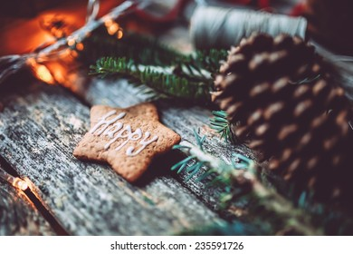 Christmas mood still life on a wooden background with pine cone, Happy holidays gingerbread cookie and lights