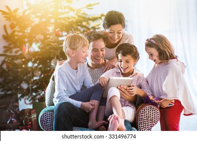 Christmas morning, cheerful family sitting in the living room having fun with the digital tablet that Santa Claus brought her, behind the decorated christmas tree, the sunshine give a cozy atmosphere