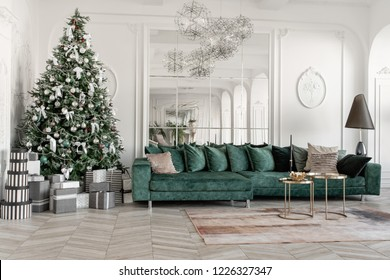 Christmas morning. classic luxurious apartments with decorated christmas tree. Living hall large mirror, green sofa, high windows, columns and stucco.