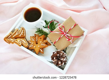 Christmas morning coffee with gingerbread cookies and gift on white tray over pink silk background