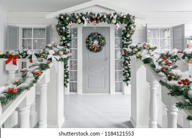 Christmas morning. house entrance decorated for holidays. Christmas decoration. garland of fir tree branches and lights on the railing