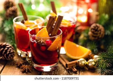 Weihnachtsmaulwein mit Gewürzen und Orangen auf einem rustikalen Holztisch. Traditionelles heißes Getränk zu Weihnachten