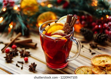 Christmas mulled red wine with spices and fruits on a wooden rustic table. Traditional hot drink at winter time.