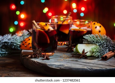 Christmas mulled red wine with spices and fruits on a wooden rustic table and christmas lights, selective focus