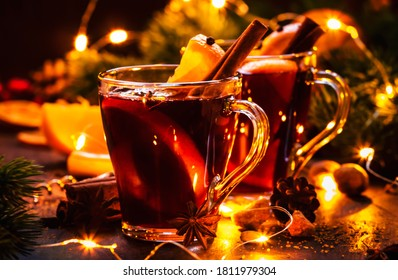 Christmas mulled red wine with spices and fruits on wooden rustic table. Traditional Christmas or New Year hot drink in festive light table setting