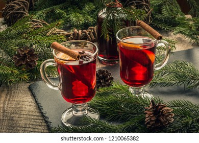 Christmas mulled wine with cinnamon and orange on wooden rustic board. Traditional hot drink at Christmas time.